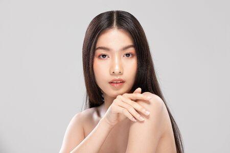 Schöne junge asiatische Frau, die beim Berühren der Schulter so glücklich und fröhlich aussieht, mit gesunder, sauberer und frischer Haut, isoliert auf weißem Hintergrund, Schönheitskosmetik-Konzept