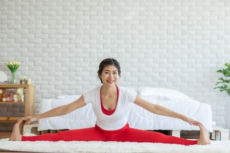 Attractive Asian woman practice yoga upavistha konasana or Seated angle pose to meditation in bedroom after wake up in the morning Feeling so comfortable and relax,Healthcare Concept 写真素材