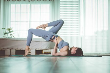 Happy Athletic Asian woman practice yoga stretching pose for stretching muscle for warm up with meditation smile after wake up in the morning Feeling so comfortable and relax,Healthcare Concept Foto de archivo