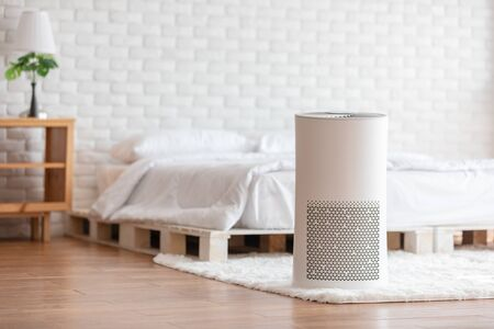 Air purifier in cozy white bed room for filter and cleaning removing dust PM2.5 HEPA in home,for fresh air and healthy life,Air Pollution Concept