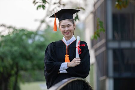 Attractive Asian Women Student Graduate in cap and gown celebrating with certificate in hand and so proud happiness in Commencement day,Congratulation of student in graduation day,Education Success