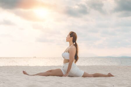 Asian young woman practice Yoga Monkey God Pose or Yoga Hanumanasana pose on the sand and beach with sunset beautiful sea in Tropical island,Feel comfortable and relax in holiday,Vacation Yoga Concept Imagens