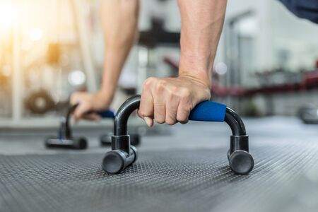 Attractive Handsome Asian young men workout with push up bar in gym focus on muscle feeling so strong and powerful,Bodybuilder concept Foto de archivo