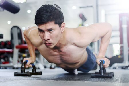 Attractive Handsome Asian young men workout with push up bar in gym focus on muscle feeling so strong and powerful,Bodybuilder concept Archivio Fotografico