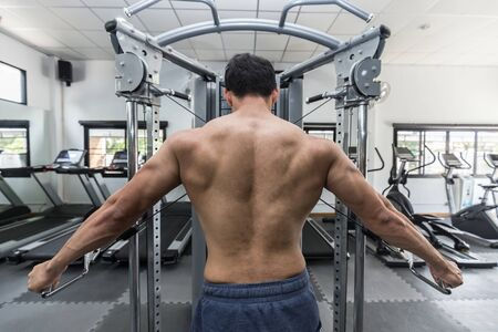 Back of view Asian men workout with cable crossover machine Concentration muscle on back for bodybuilding feeling so strong and powerful,Bodybuilder Concept