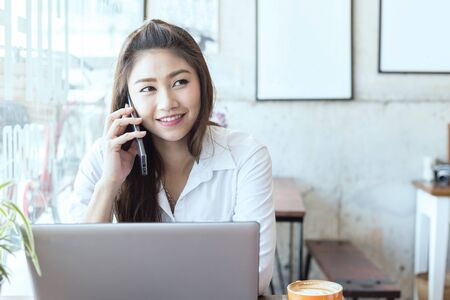 Beautiful Attractive Asian woman working with laptop smile and talking with customer in smartphone to get idea and requirement for success her job outside office in coffee shop cafe,Business Concept