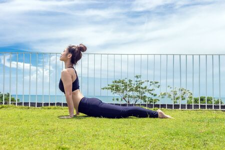 Happy Asian woman wearing black sport wear practice yoga Cobra pose with beautiful sea view,Feeling so comfortable and relax in holiday