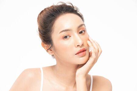 Belle femme asiatique touchant un sourire doux aux joues avec une peau propre et fraîche Bonheur et gaie avec des émotions positives, isolées sur fond blanc, Concept de beauté et de cosmétiques