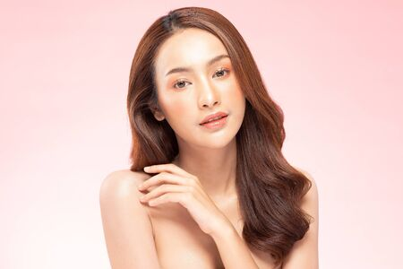 Beautiful Asian woman smile with clean and fresh skin Happiness and cheerful with positive emotional,isolated on pink background,Beauty Cosmetics and spa Treatment Concept Standard-Bild