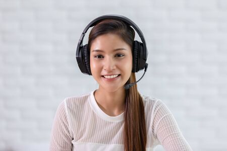 Camera view of Happy young asian business woman wears headset talk to online video conference call with her business team during quarantine covid-19 self isolation at home,VDO Call Conference Concept Banco de Imagens