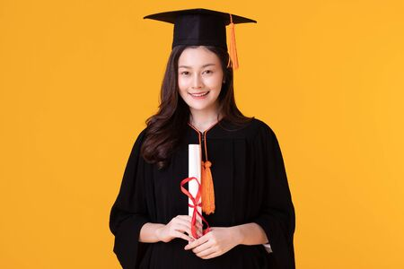 Happy Graduate asian woman in cap and gowm holding Certificated or diploma on yellow background,Summer Graduation Concept