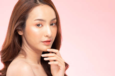Beautiful Asian woman smile touching chin with clean and fresh skin Happiness and cheerful with positive emotional,isolated on pink background,Beauty Cosmetics and spa Treatment Concept