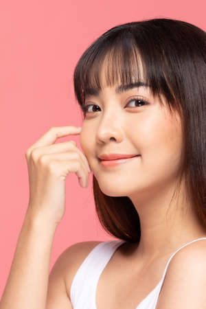 Beautiful Asian woman touching soft cheek smile with clean and fresh skin Happiness and cheerful with positive emotional,isolated on pink background,Beauty Cosmetics and spa Treatment Concept