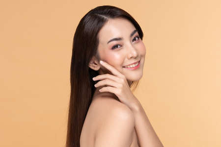Beautiful Asian woman looking at camera smile with clean and fresh skin Happiness and cheerful with positive emotional,isolated on Beige background,Beauty Cosmetics and spa Facial treatment Concept Archivio Fotografico
