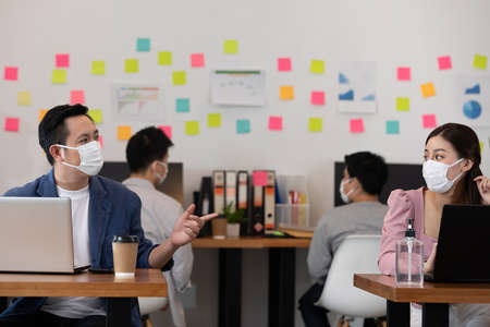 New normal of Business man and woman wearing face mask meeting and working together for discussion and brainstroming to get ideas or marketing solution with social distance due virus pandemic