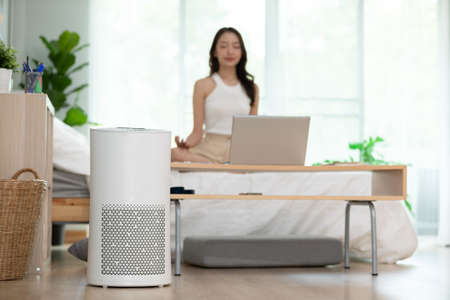Air purifier in cozy white Living room for filter and cleaning removing dust PM2.5 HEPA at home with woman exercise yoga in background,for fresh air and healthy life,Air Pollution Concept
