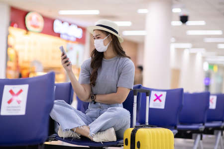 Asian young woman traveller wearing face maks using mobile phone at airport Due Covid-19 flu virus pandemic and protection