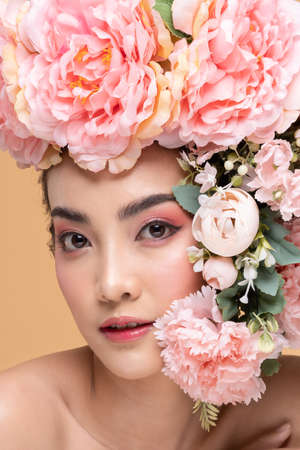 Beauty Asian young woman with big bouquet flowers on head smile with clean fresh skin Happiness and cheerful with positive emotional on Beige background,Beauty Cosmetics and Facial treatment Concept
