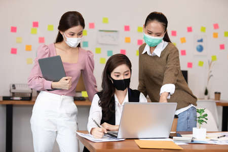 Group of business young woman wearing face mask meeting and working together for discussion and brainstroming to get ideas or marketing solution with social distance due virus pandemic