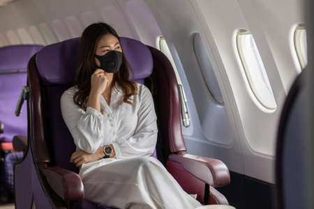 Asian young woman wearing protective mask sitting near windows at first class on airplane during flight,Traveling and Business during COVID-19 virus pandemic concept