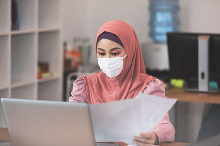 New normal of Asian business Muslim or islam women wearing face protective mask in casual working with laptop and smile looking at camera at modern office or Co-Working Space,Business Startup Concept