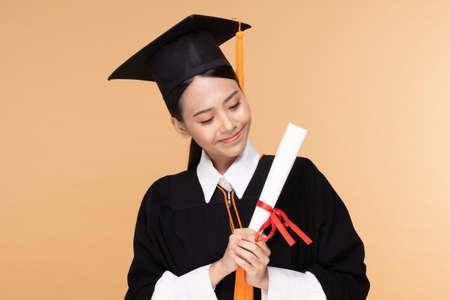 Happy Graduate asian woman in cap and gowm holding Certificated or diploma on Beige background,Graduation Concept