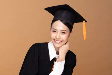 Beautiful Attractive Asian woman graduated in cap and gown smile so proud and happiness,Isolated on Beige background,Education Success Concept