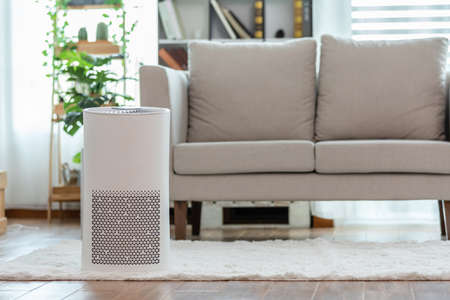 Air purifier in cozy white Living room for filter and cleaning removing dust PM2.5 HEPA in home,for fresh air and healthy life,Air Pollution Concept
