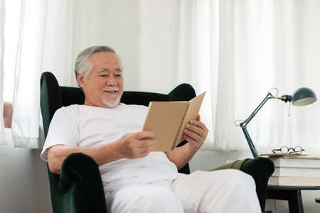 Asian Elderly man with white hairs sitting on sofa reading book ralax and cozy at home Фото со стока