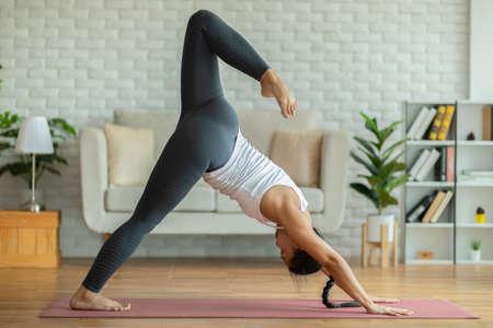 Calm of Beautiful Attractive Asian woman practice yoga Downward Facing dog one leg or yoga Eka Pada Adho Mukha Svanasana pose to meditation with yoga in bedroom,Recreation in holidays concept