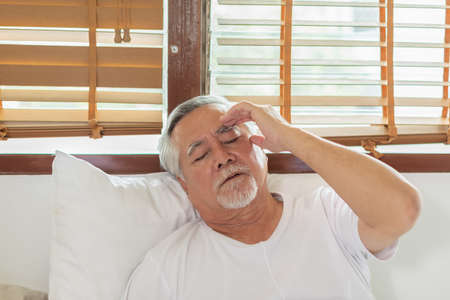 Asian Elderly senior man white hairs headache and migraine so pain and illness,Stress senior man sit on bed at home alone,unhappy elderly touch on head serious and tried,Unhappiness Elderly concept