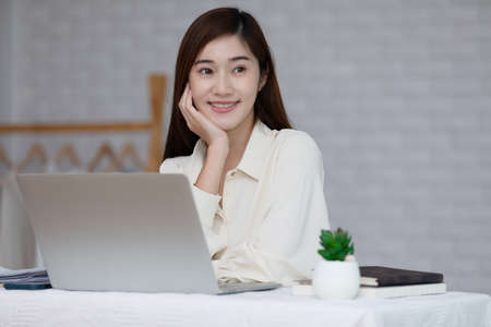 Happy Asian young business woman working at home with computer laptop and smile,Entrepreneur of young woman thinking about business plan smile and cheerful for growth value of her business startup