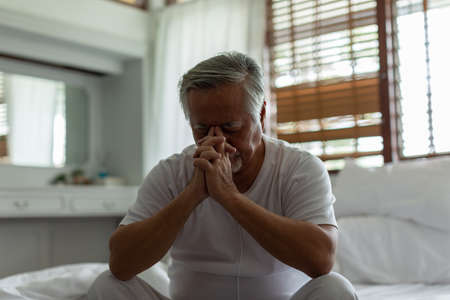 Asian Elderly senior man white hairs headache and migraine so pain,Stress senior man sit on bed at home alone,unhappy elderly touch on head serious and tried,Unhappy Elderly despond concept,Low key Zdjęcie Seryjne