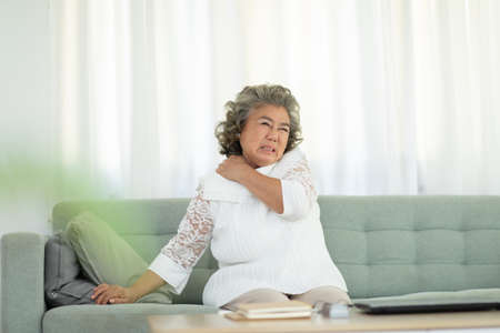 Asian Elderly senior woman with white hairs neck and shoulder pain and illness on sofa alone at home,Elderly Care and insurance Concept