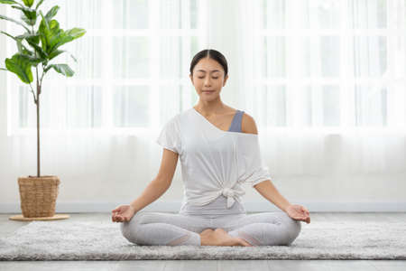 Calm of wellness Asian young woman sit on carpet breathing with yoga lotus pose,Yoga meditation of young healthy woman relax and comfortable at white cozy home,Yoga Exercise for Wellness Concept