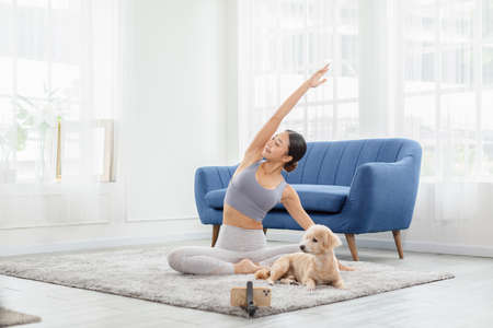 Wellness Athlete Asian indian woman looking mobile phone practice yoga online class stretching muscle with dog at home to meditation.Yoga Exercise Class Concept,Self isolation due COVID-19 pandemic Standard-Bild