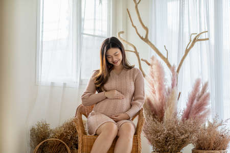 Happy Pregnant Woman sitting on couch holding and stroking her big belly at cozy home,Pregnancy of young woman enjoying with future life relax at home,Motherhood and Pregnant Concept,Soft focus