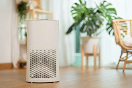 Air purifier in cozy white living room for filter and cleaning removing dust PM2.5 HEPA and virus in home,for fresh air and healthy Wellness life,Air Pollution Concept