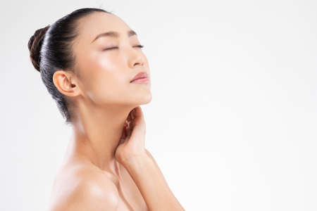 Relaxing Asian young woman close her eyes touch her neck deep breath and comfortable.Calm of wellness beautiful japanese woman resting with healthy pure and fresh skin after spa facial treatment Standard-Bild