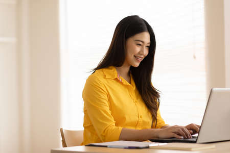 Entrepreneur beautiful business asian young woman wear yellow shirt work online with laptop at home.Freelance woman working online sale marketing at home.Small Business Startup concept.Tracking Shot