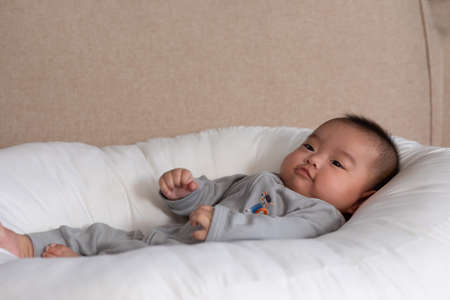 Adorable Asian baby girl lying on bed looking at camera.Cute little baby smiling and happiness relaxing in bed.Portrait of asian baby newborn in bedroom Standard-Bild