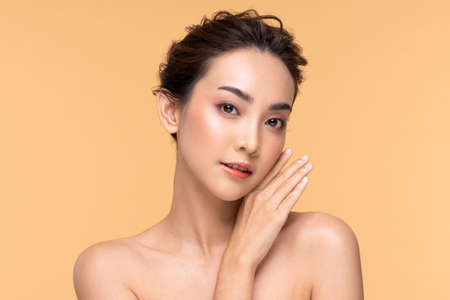 Beautiful Asian young woman touching soft cheek smile with clean fresh skin Happiness and cheerful with positive emotional,isolated on Beige background,Beauty Cosmetics and Facial treatment Concept