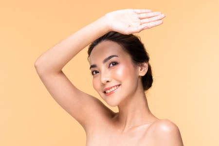 Beautiful Asian young woman hand up cover face protet sun light and UV smile with clean fresh skin Happiness and cheerful ,isolated on Beige background,Beauty Cosmetics and Facial treatment Concept Standard-Bild