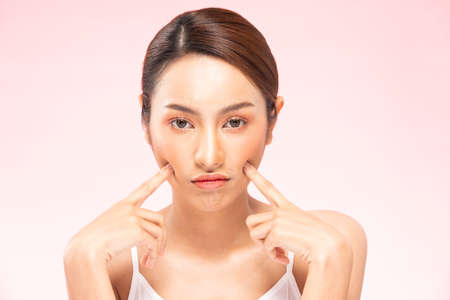 Unhappy Asian woman touching her cheek worry dry skin.Skin problem of beauty asian young woman having trouble of Dry skin, acne and wrinkles on pink background.Skin Problem Concept