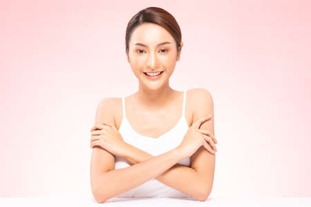 Beautiful Young Asian Woman cross arms smile feeling so happy and confident with healthy Clean and Fresh skin,isolated on pink background,Beauty Cosmetic Concept