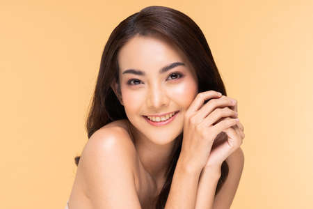 Young Beautiful Asian woman smile holding hands with clean and fresh skin Happiness and cheerful with positive emotional,isolated on Beige background,Beauty Cosmetics and spa Treatment Concept Standard-Bild