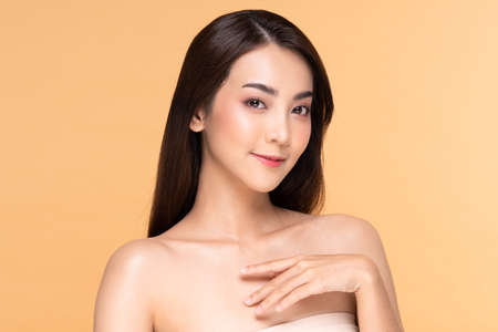 Beautiful Asian woman looking at camera smile with clean and fresh skin Happiness and cheerful with positive emotional,isolated on Beige background Standard-Bild