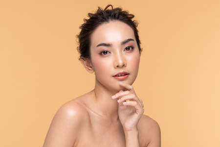 Beautiful Asian woman touching chin smile with clean and fresh skin Happiness and cheerful with positive emotional,isolated on Beige background,Beauty Cosmetics and spa Facial treatment Concept