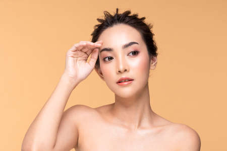 Beautiful Asian woman touching eyebrow smile with clean and fresh skin Happiness and cheerful with positive emotional,isolated on Beige background,Beauty Cosmetics and spa Facial treatment Concept