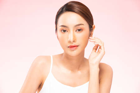 Young Beautiful Asian woman smile touching soft cheek with clean and fresh skin Happiness and cheerful with positive emotional,isolated on pink background,Beauty Cosmetics and spa Treatment Concept